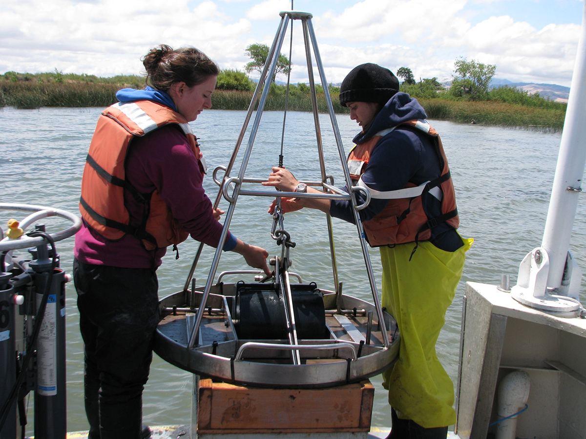 two graduate students deploy sampling equipment off stern